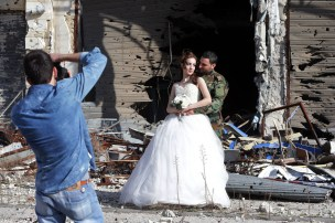 Newly-wed Syrian couple Nada Merhi,18, and Hassan Youssef,27, have their wedding pictures taken in front of a heavily damaged building in the war ravaged city of Homs on February 5, 2016. A Syrian photographer thought of using the destruction of Homs to take pictures of newly wed couples to show that life is stronger than death. / AFP / JOSEPH EID (Photo credit should read JOSEPH EID/AFP/Getty Images)