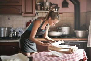 young woman rolling dough for baking in kitchen