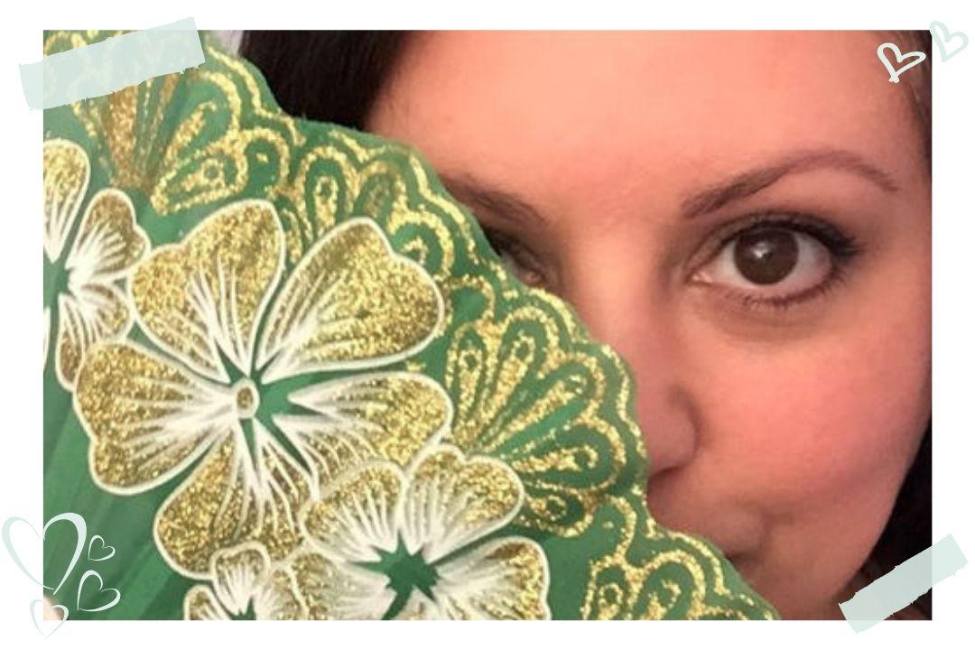 Donna DeRosa holding a green fan