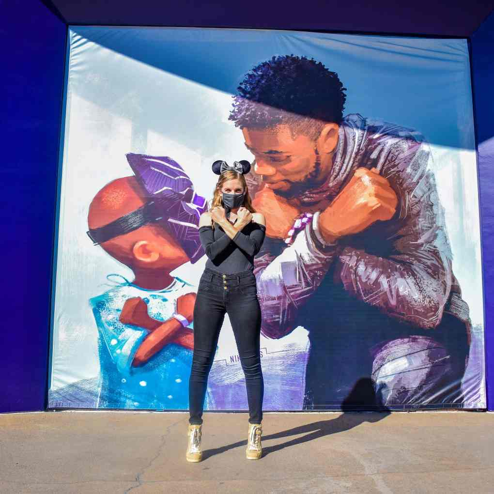 """A mural in Downtown Disney Anaheim of Chadwick Boseman and a male child wearing a Black Panther mask. Both posing with the """"Wakanda"""" arm crossing. I am standing in front of the mural in all black doing the same arm crossing."""
