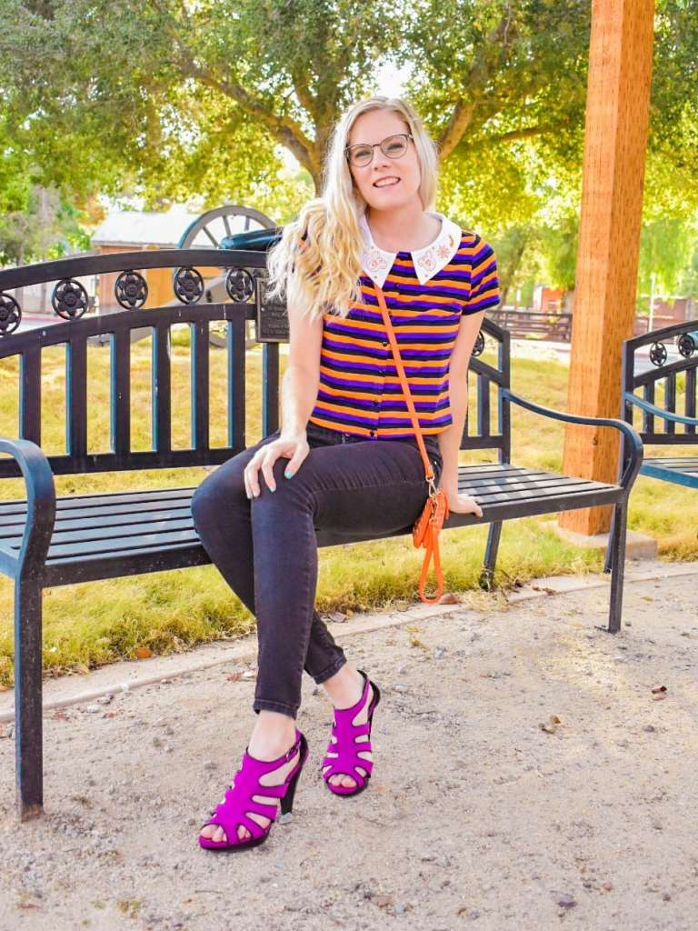 Located in a bright, fall setting, I am showing how to style this crop top from Her Universe for the Halloween season. I matched the colors of the stripes in the shirt to my outfit. I am wearing a pair of black high-waisted pants, an orange crossbody bag, and a pair of electric purple heels. I am posing on a bench so you can easily see the entire outfit.