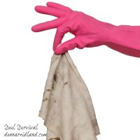 Human hand in glove holding dirty rag, isolated on white
