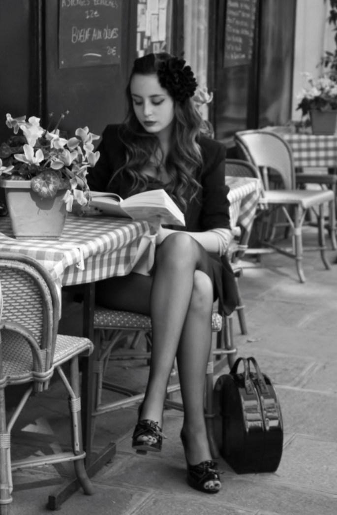 woman reading a book at parisian cafe