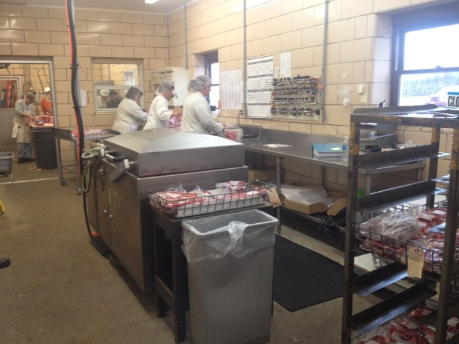Employees wrapping meat