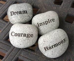 Rocks with the words Dream, Inspire, Courage and Harmony printed on them.
