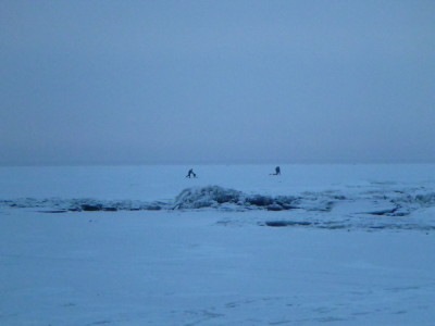 Skaters and fishermen on ice in Parnu Bay