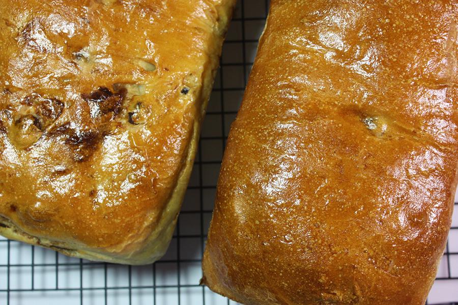 2 loaves of baked cinnamon raisin bread on wire rack