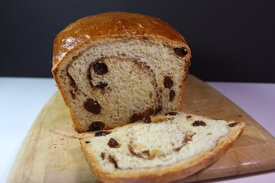 baked loaf of cinnamon raisin bread sliced on wooden cutting board