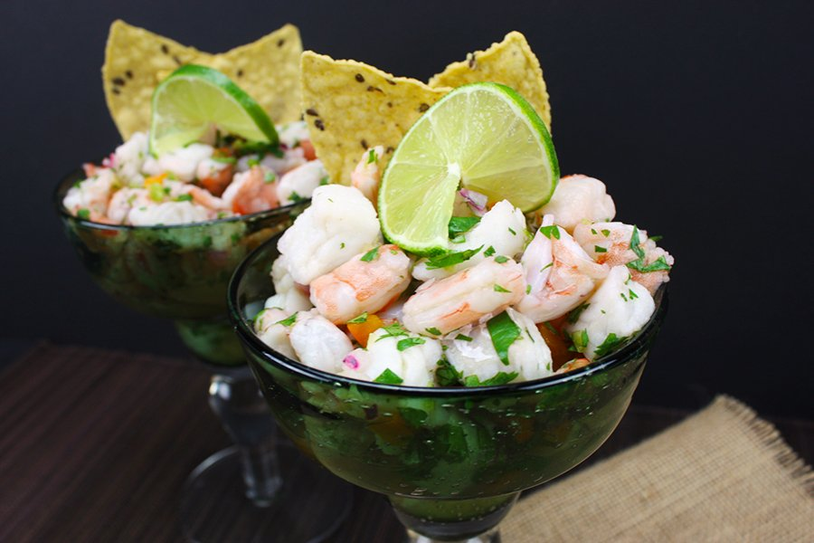 Ceviche in two green margarita glasses garnished with tortilla chips and lime slice