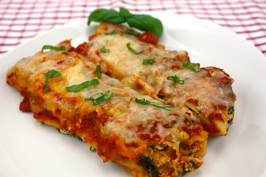two manicotti on white plate garnished with fresh basil