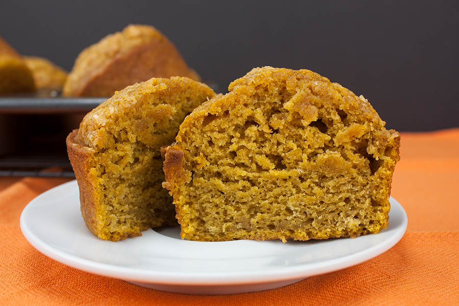 pumpkin muffin sliced in half on white plate orange tablecloth