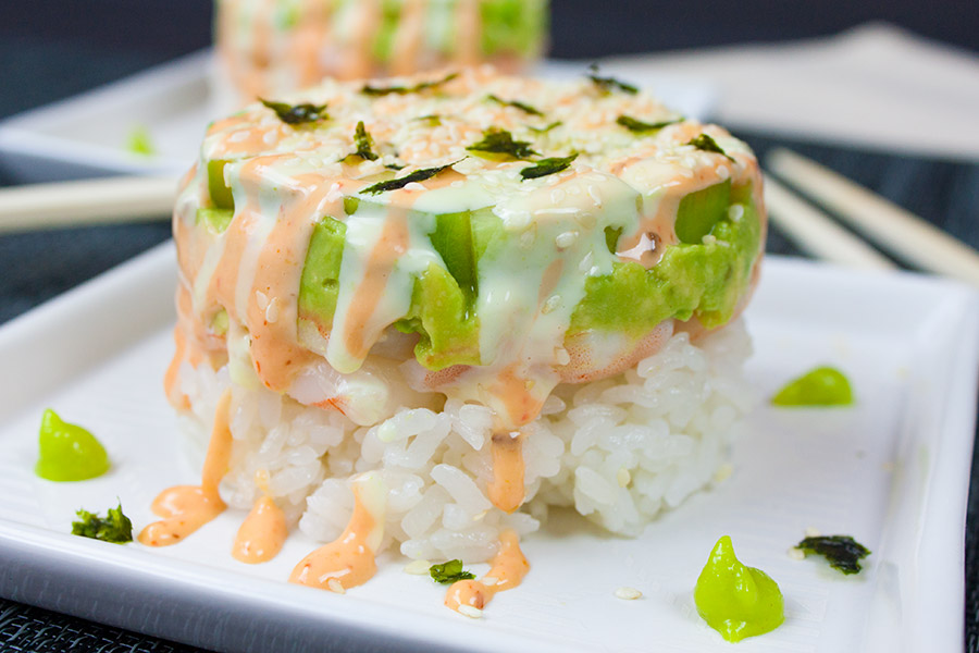 spicy shrimp sushi stack on white plate with wasabi sauce dots