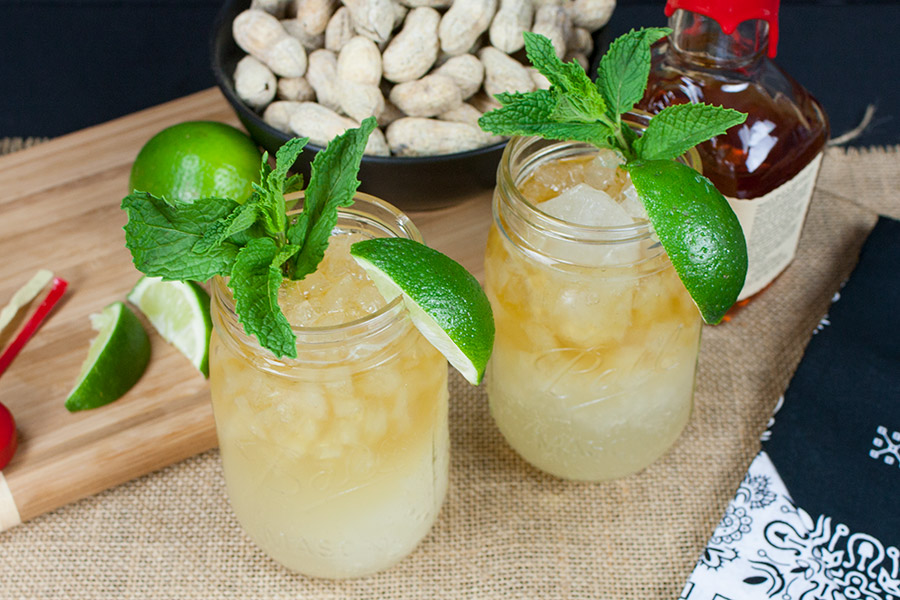two Kentucky Mule drinks in mason jars garnished fresh mint lime wedges black bowl of peanuts in the shell