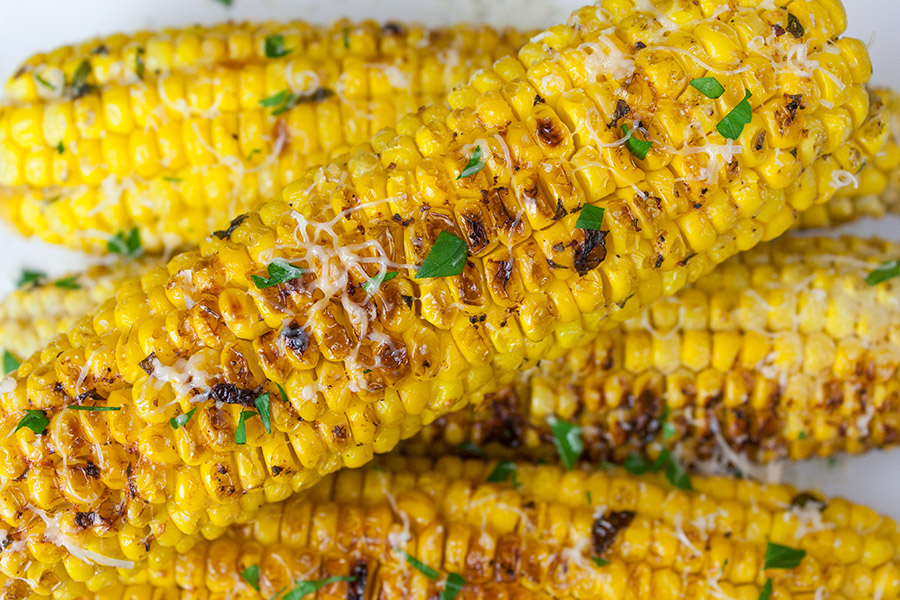 Grilled Parmesan Corn On The Cob garnished with cheese and parsley