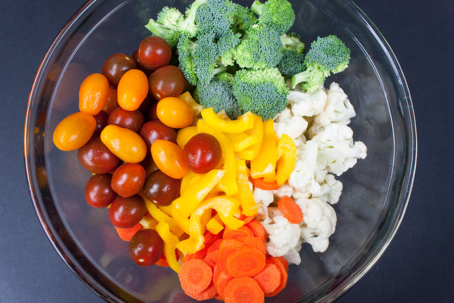 raw broccoli florets, raw cauliflower florets, raw carrots, raw yellow pepper and cherry tomatoes in glass mixing bowl