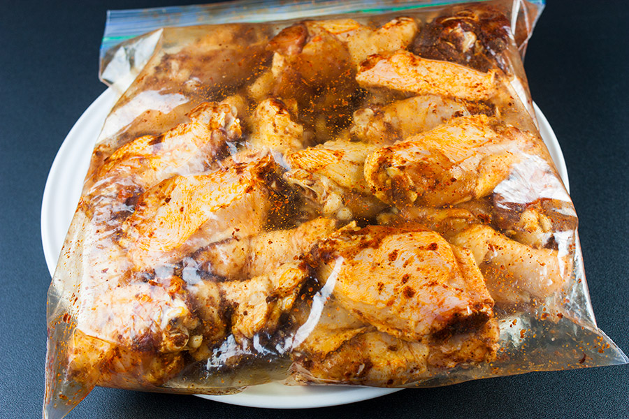 chicken wings coated with dry rub in gallon zip top bag