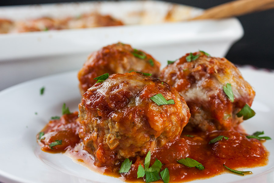 3 Parmesan Meatballs on white plate covered with tomato sauce garnished with chopped parsley