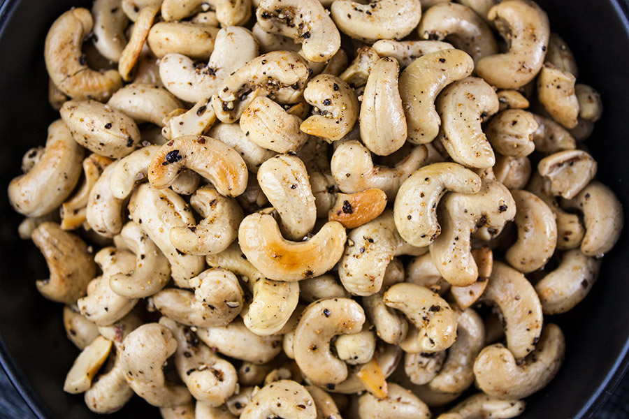 close up of Salt and Pepper Roasted Cashews in black bowl