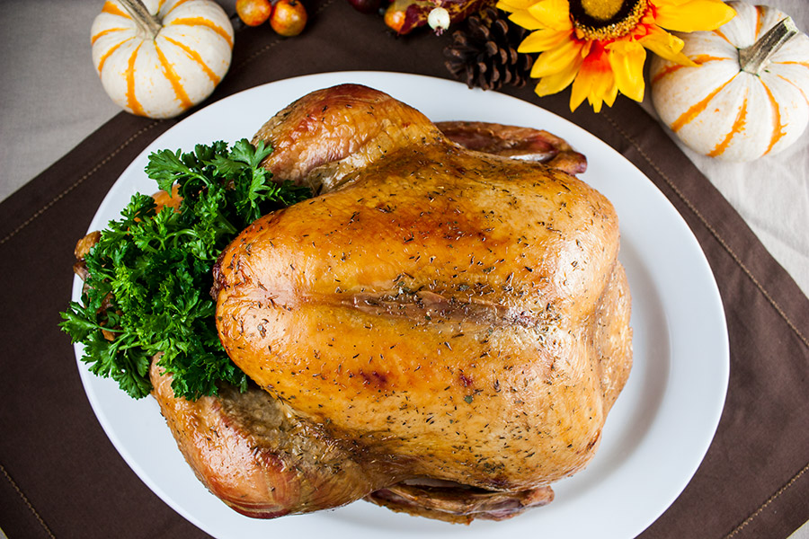 whole roasted golden brown turkey on a white serving platter garnished with parsley
