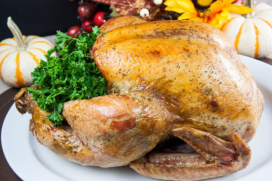 Dry Brined Roast Turkey with parsley garnish on a white platter