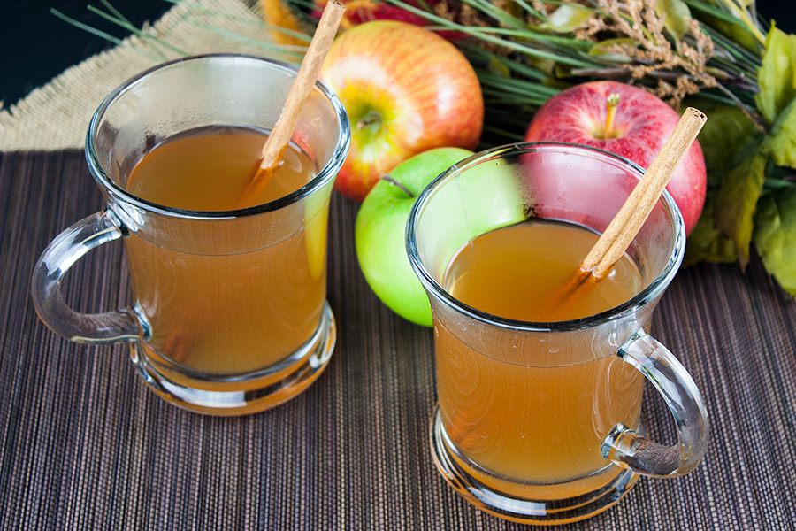 two clear glass mugs filled with apple cider cinnamon stick garnish