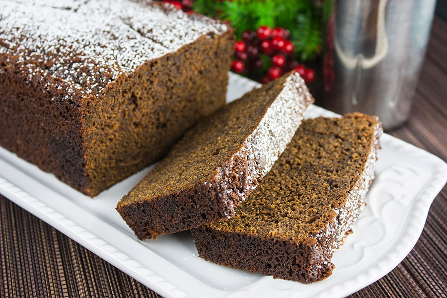 gingerbread loaf with two slices on a white plate