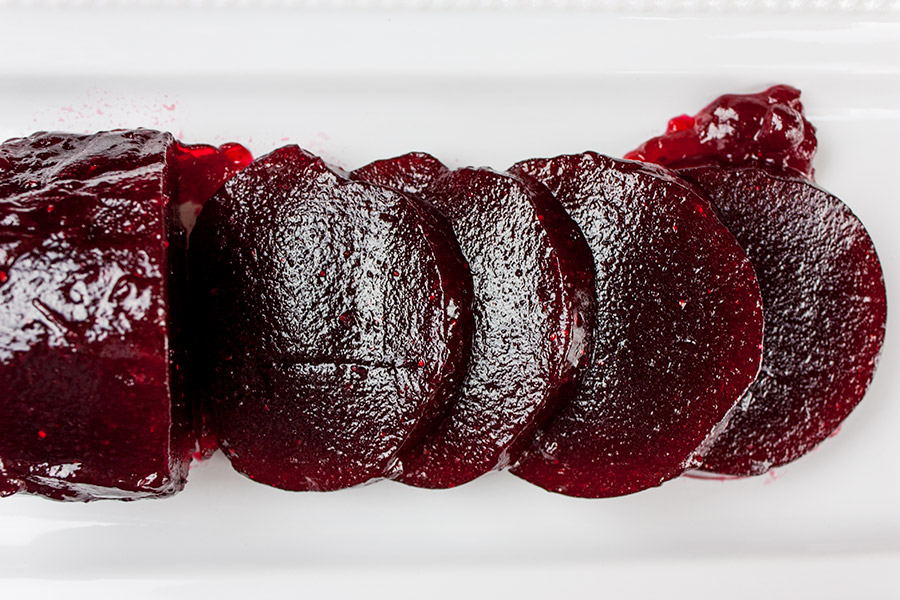 unmolded cranberry sauce shaped like a jar and sliced in serving pieces on a white platter