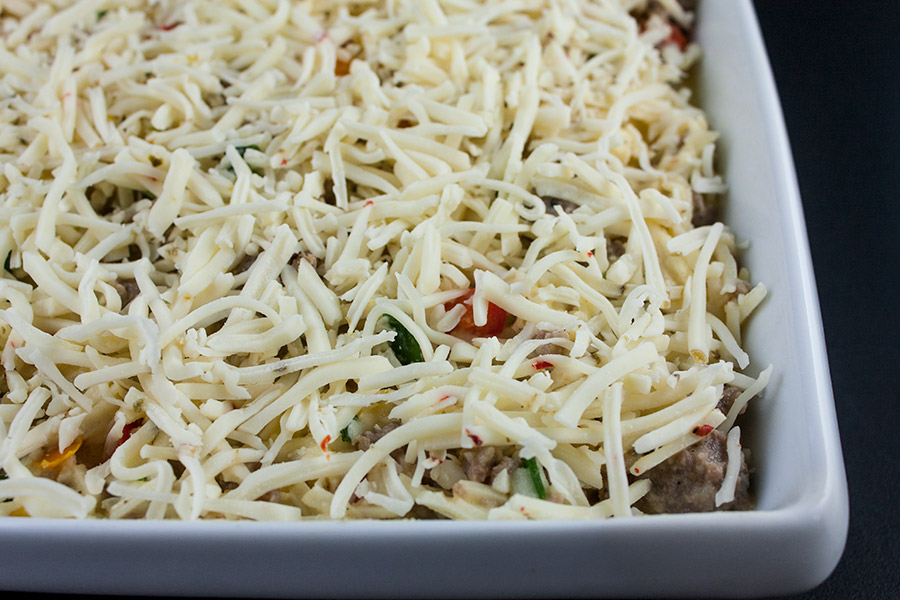sausage hash brown breakfast casserole mixture in a white baking pan with shredded pepper jack cheese sprinkled over the top