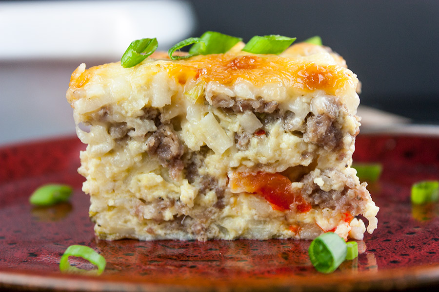 serving slice of sausage hash brown casserole on red pottery plate