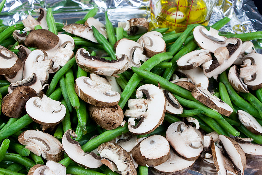 cleaned and diced green beans and mushrooms on a foil lined baking sheet