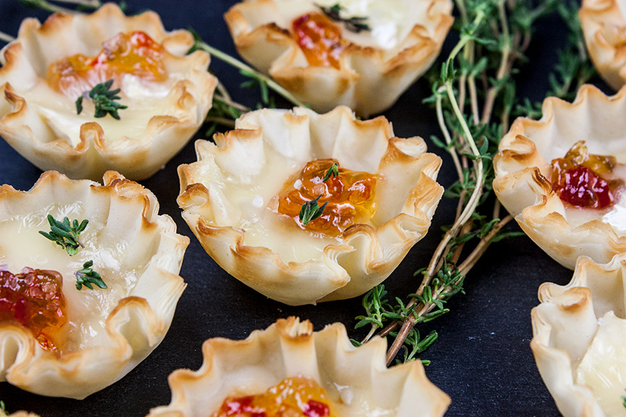 Pepper Jelly Brie Bites arranged on slate garnished with fresh thyme sprigs