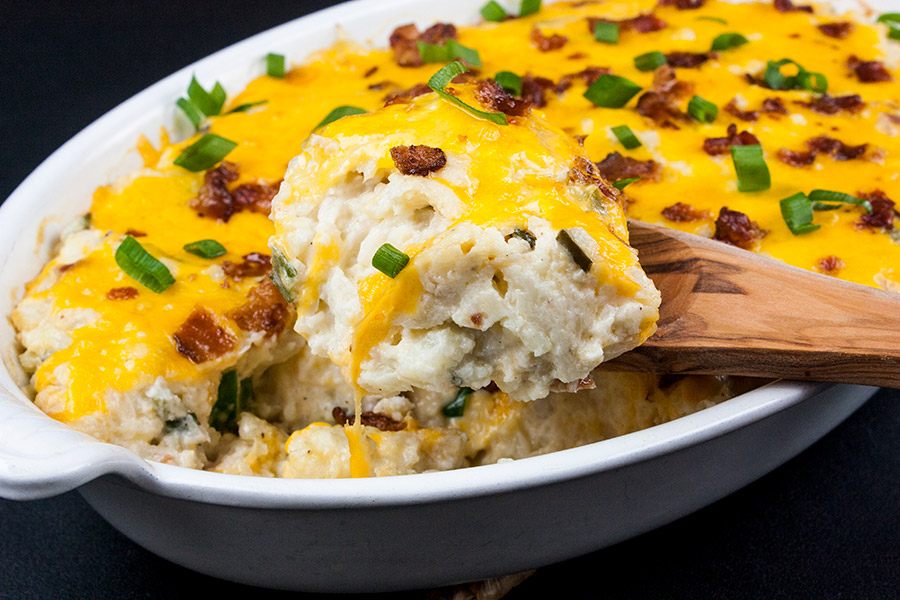 loaded cauliflower mash casserole in white oval dish with wooden spoon