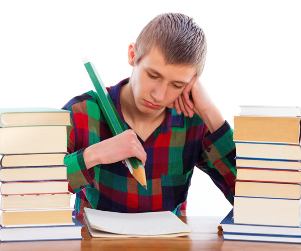 A young adult man sitting at a desk surrounded by stacks of books is ready to write in a notebook with an awkwardly large pencil. This symbolizes the difficulty some dyslexic adults have with writing and reading in a hurry. Once a dyslexic accepts that they will always need extra time for reading and writing, they can plan for it and understand that that aspect of their dyslexia is as good as it gets.