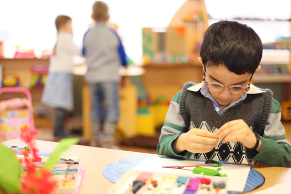 A picture of a young boy in a classroom who is completely absorbed in building something at his table while children play in the background.