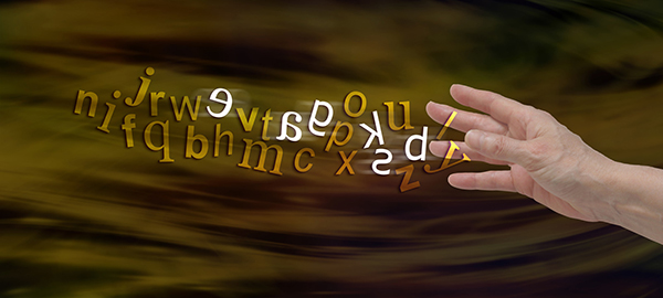 A symbolic image picturing a flow of jumbled letters facing backwards and forwards leaving a person's hand. Many adults living with dyslexia do not know they have it. What can be done?
