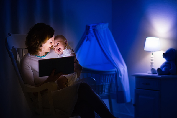 A mom sits n a rocking chair in a dim nursery and reads a bedtime story to her baby as they laugh together. Shared reading and attachment theory work together to create strong bond between parent and child and to teach vital preliteracy skills.
