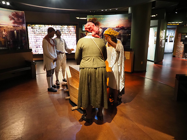 Photo from a different angle of an exhibit at the African Burial Ground National Monument depicting five life-size mourners gathered around two coffins.