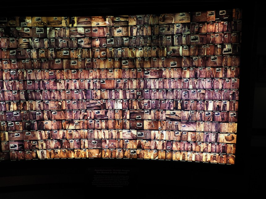 Photograph of an exhibit at the African National Burial Monument showing many photos of coffins that were respectfully studied and documented before being re-interred.