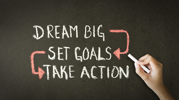 Writing on a chalkboard that says Dream Big, Set Goals, Take Action