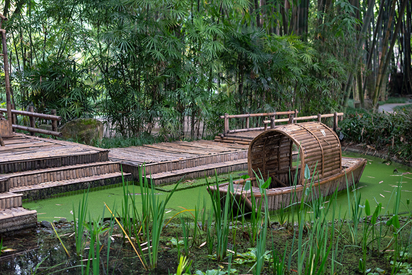 A bamboo boat drifts in a green, plant-filled pond surrounded by bamboo walkways inside a bamboo forest in the Sichuan province of China.