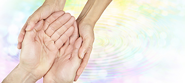 Two sets of hands rest in each other over a background of rippling water shaded in pastel tones. The picture is meant to express kindness.