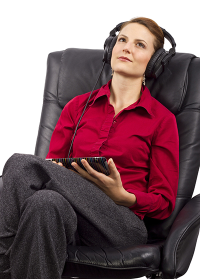 A woman sits in a desk chair wearing a pair of headphones as she listens to an audiobook on her tablet.