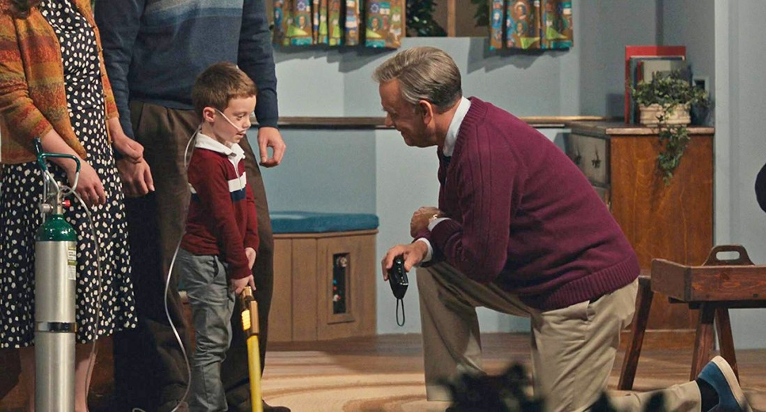 Mr. Rogers shows his skill at interpreting behavioral issues in children as he knewwls down to talk to a troubled child in a scene from the movie A Beautiful Day in the Neighborhood.