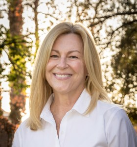 Photo of Kim Jocelyn Dickson, author of The Invisible Toolbox: The Power of Reading to Your Child from Birth to Adolescence. she has blond hair and wears a white button down shirt. There are trees in the background.