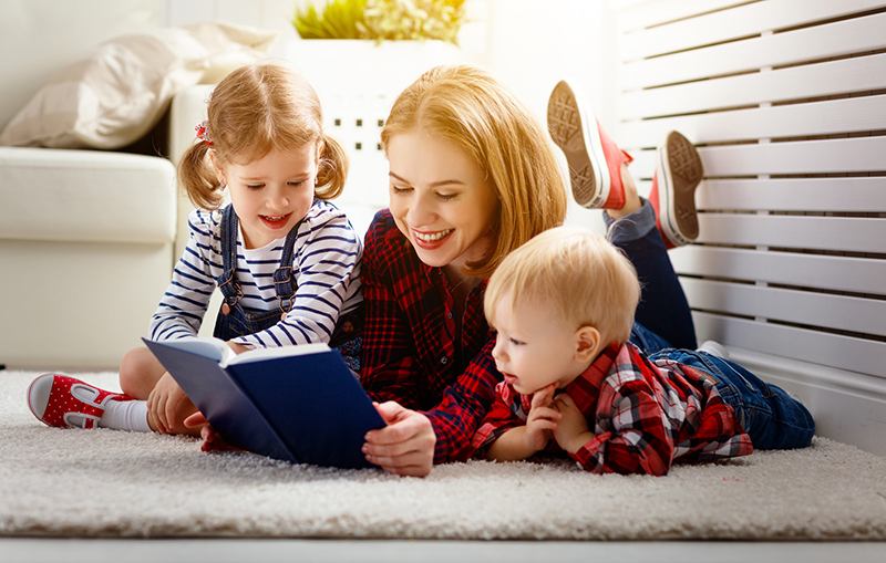 A mother reads aloud to her two young children because she is raising readers from birth to give them the tools they need to succeed when they enter school.