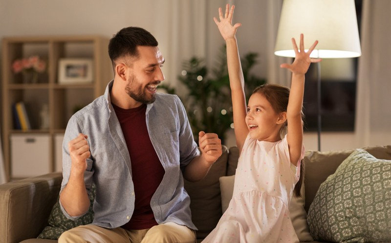A father and school-age daughter sitting together on the couch celebrate a small victory together. The girl throws her hands up in the air. Celebrating small victories can help a dyslexic child develop a positive mindset.