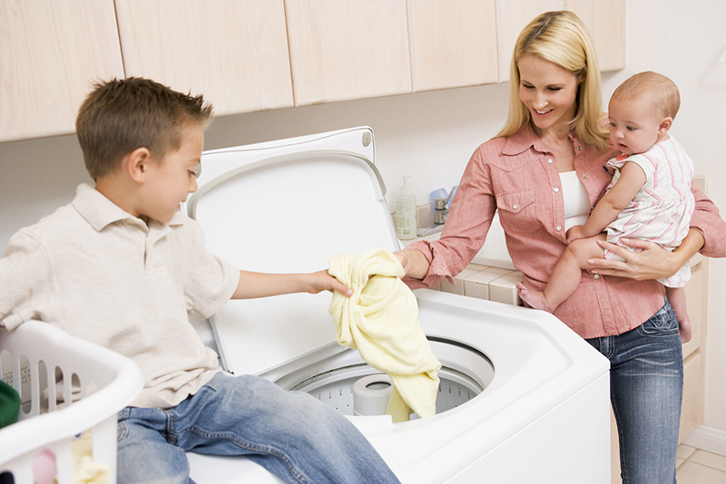 A mother and son and baby load the washing machine together. Working and schooling from home requires extra kindness and cooperation to help families exist peacefully during troubled times and to help kids focus on school and avoid COVID academic slide.