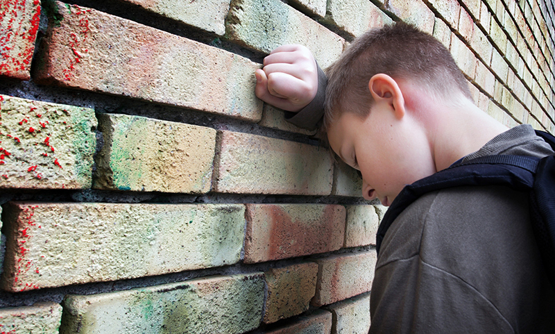 A frustrated boy leans his head on his arm against a brick wall, looking sad and defeated. How can parents help dyslexic children adapt to virtual school?