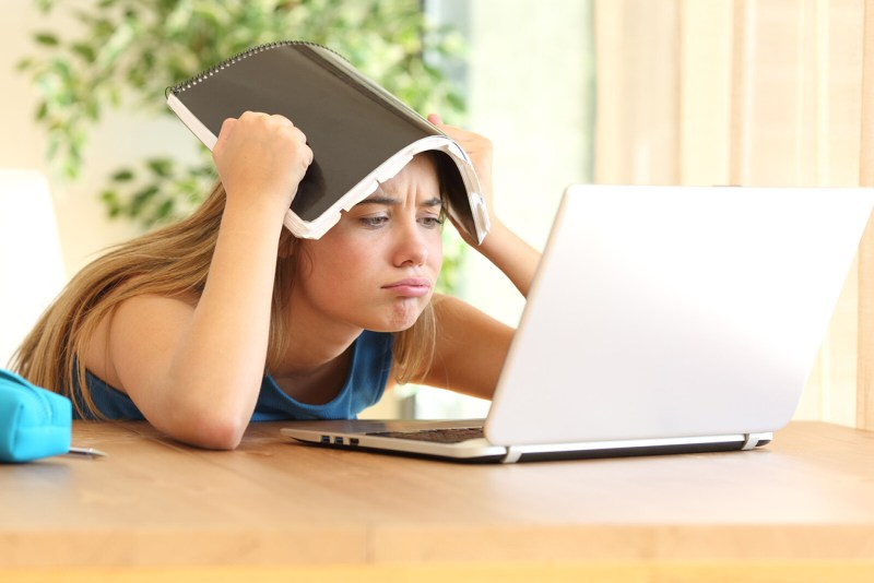 A frustrated high school age girl holds a notebook over her head as she stares at the screen of her laptop. Parents can help children cope with the psychological challenges of distance learning by making health and well-being a priority.