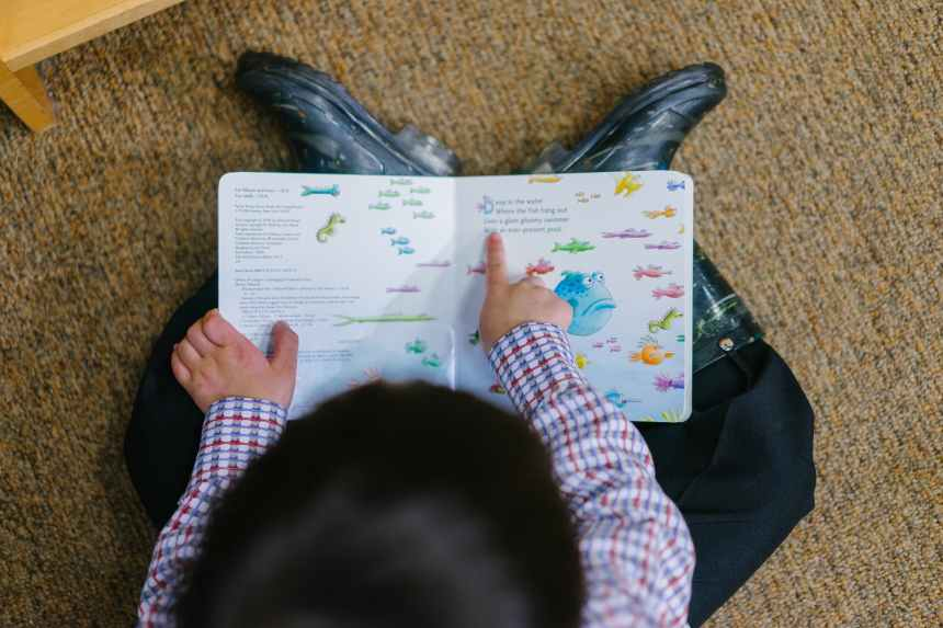 Photo from overhead as a little boy reads from a colorful board book, using his finger under the words as he reads from left to right. Parents who see that their child has reading and learning challenges at home can help their child learn to do this and other things to help.